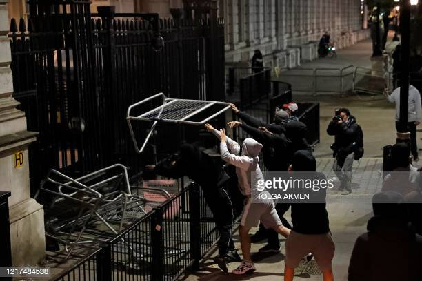 Protestors throw barriers towards the gates of Downing Street during an antiracism demonstration in London on June 3 after George Floyd an unarmed...