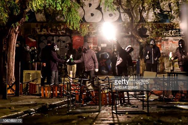 Protestors throw petrol bombs to antiriot policemen in Athens on November 17 during clashes following a rally commemorating the 1973 students...