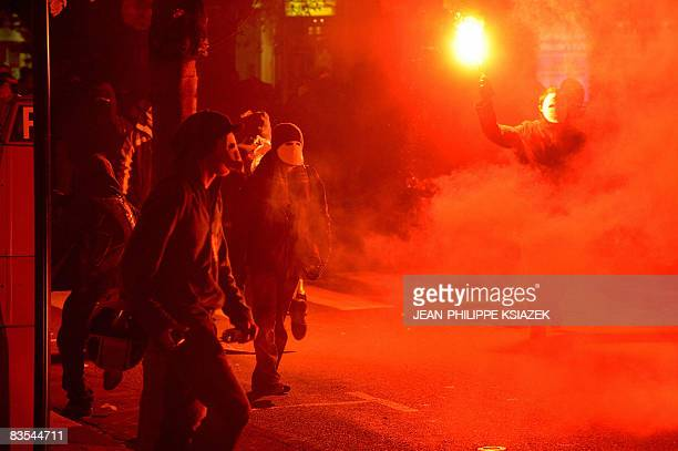 Protestors throw smoke grenades in the streets of the central France city of Vichy during a demonstration against a conference gathering 27 European...