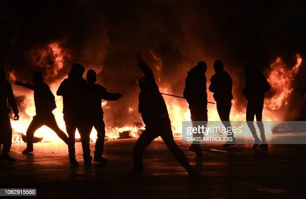Protestors throw stones in Thessaloniki on November 17, 2018 during clashes following a rally commemorating the 1973 students uprising against the...