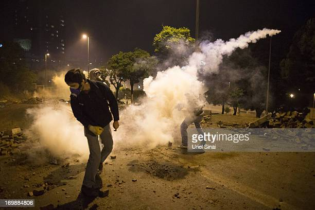 Protestors throw tear gas back at Turkish police during clashes with Turkish police near Turkish prime minister Recep Tayyip Erdogan office between...