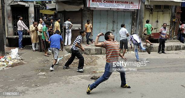 Protestors throwing stones on Police during a clash between protestors and Indian police officials on August 10 2013 in Jammu India A town in the...