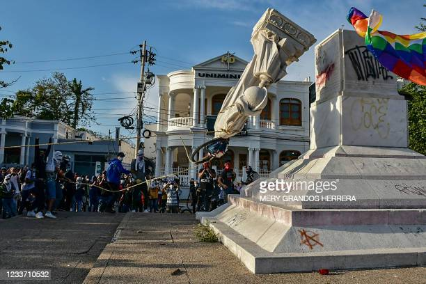 Protestors topple a statue of Christopher Columbus during a demonstration against government in Barranquilla, Colombia on June 28, 2021.