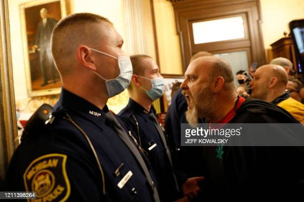 TOPSHOT Protestors try to enter the Michigan House of Representative chamber and are being kept out by the Michigan State Police after the American...