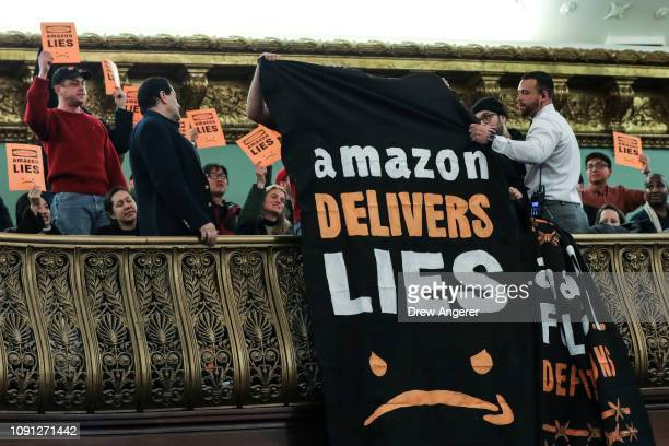 Protestors unfurl antiAmazon banners from the balcony of a hearing room during a New York City Council Finance Committee hearing titled 'Amazon HQ2...