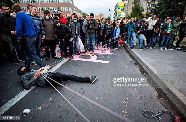 TOPSHOT Protestors use an improvised slingshot to throw balloons filled with colored paint toward the Parliament building during an antigovernment...