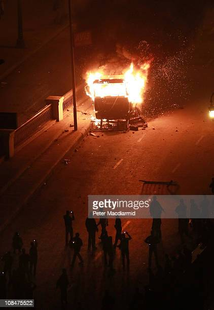 Protestors use their mobile telephones to photograph a burning police vehicle during clashes on January 28 2011 in Cairo EgyptThousands of police are...