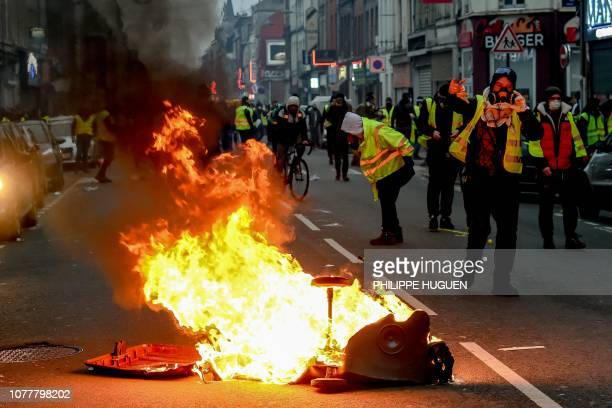 Protestors walk by a burning trash can during a yellow vest antigovernment demonstration in Lille northern France on January 5 2019 The yellow vest...