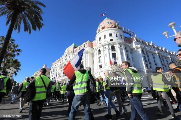 Protestors walk in front of the 'Negresco' hotel on the 'Promenade des Anglais' during a protest of Yellow vests against rising oil prices and living...