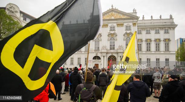 Protestors watch Martin Sellner leader of the farright Identitarian Movement in Austria speak as they gather together in front of the Austrian...