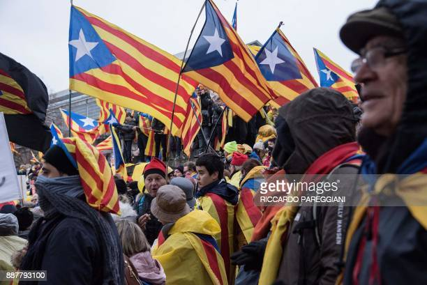 Protestors wave Catalan 'Estelada' flags and banners as they attend a proindependence demonstration in Brussels on December 7 2017 A sea of around...