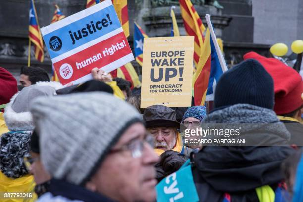 Protestors wave Catalan 'Estelada' flags and placards as they attend a proindependence demonstration in Brussels on December 7 2017 A sea of around...