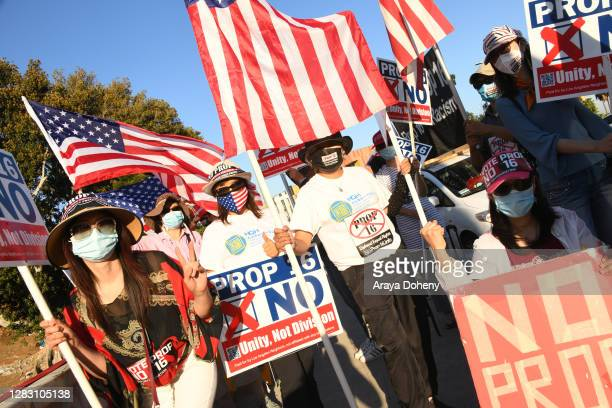 Protestors wear protective masks and wave American flags as they demonstrate against Prop 16 on a freeway overpass downtown on October 30, 2020 in...