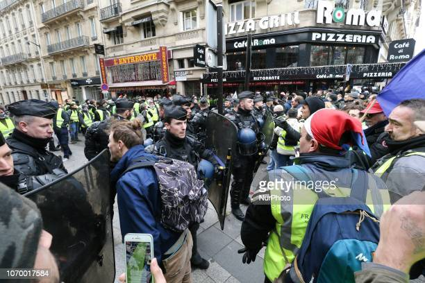 Protestors wearing a quotyellow vestquot face riot police officers as they demonstrate against rising costs of living in front of the Arc de Triomphe...