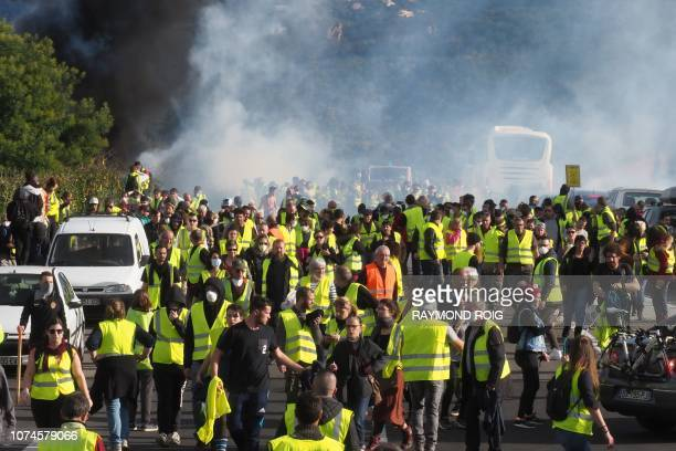 Protestors wearing a yellow vest demonstrate against rising costs of living they blame on high taxes at the A9 highway toll of Le Boulou southern...
