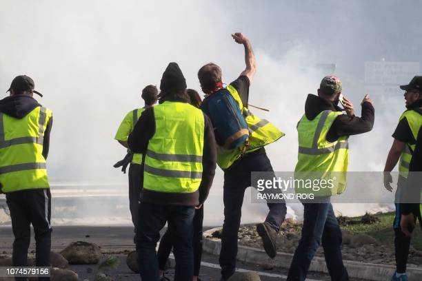 Protestors wearing a yellow vest face French riot police as they demonstrate against rising costs of living they blame on high taxes at the A9...