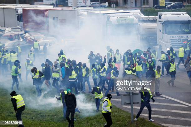 Protestors wearing a yellow vest stand amid smoke during a demonstration against rising costs of living they blame on high taxes in Mondeville near...