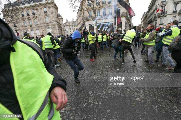 Protestors wearing a yellow vest stand amid tear gas during clashes with riot police on the Champs Elysees avenue during a demonstration against...