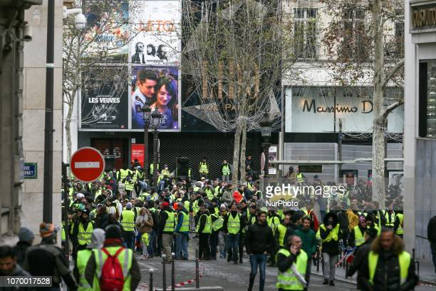 Protestors wearing a yellow vest stand in front of the famous Lido French cabaret on the Champs Elysees avenue during a demonstration against rising...