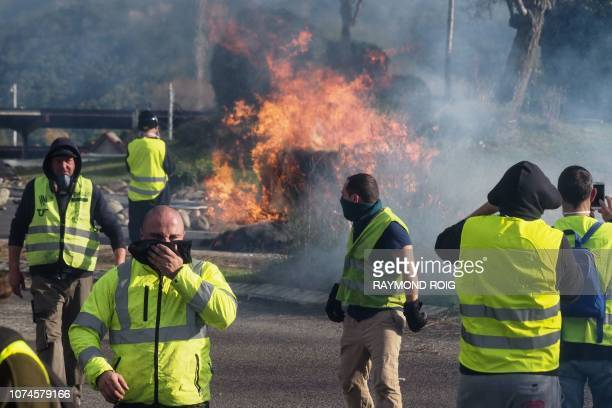 Protestors wearing a yellow vest stand next to a burning barricade as they demonstrate against rising costs of living they blame on high taxes at the...