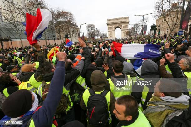 Protestors wearing a yellow vest stand on the Champs Elysees avenue with a French flag during a demonstration against rising costs of living in Paris...