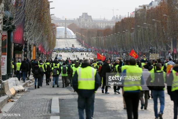 Protestors wearing a yellow vest walk on the Champs Elysees avenue during a demonstration against rising costs of living in Paris on December 8 2018...