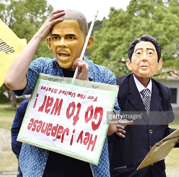 Protestors wearing face masks of US President Barack Obama and Japanese Prime Minister Shinzo Abe display messages objecting to their security...