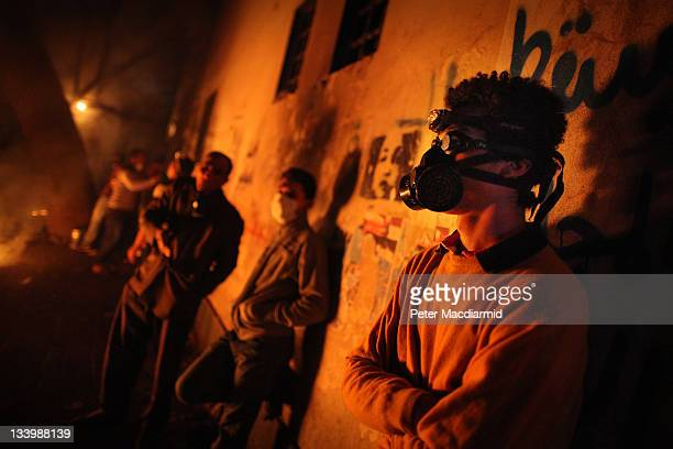 Protestors wearing gas masks stand in Mohammed Mahmoud Street during clashes with police on November 23 2011 in Cairo Egypt Thousands of Egyptians...