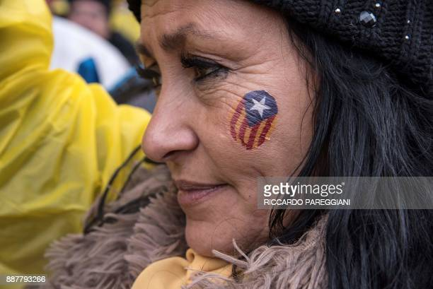 A protestors wears a Catalan 'Estelada' flag on her cheek as she attends a proindependence demonstration in Brussels on December 7 2017 A sea of...