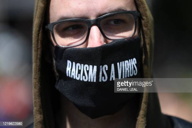 A protestors wears a facemask in support of the Black Lives Matter movement as they march near Marble Arch station central London on June 13 in the...