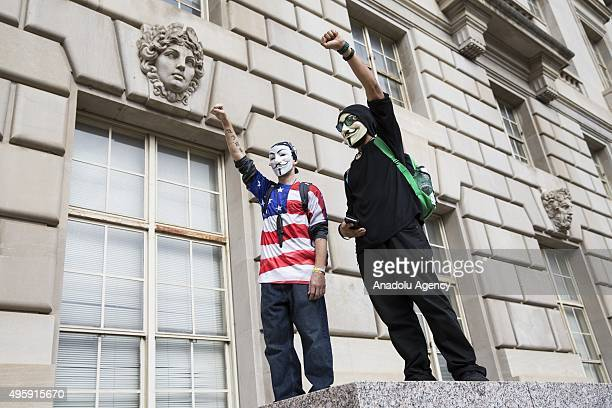 Protestors with raised fists stand on a barrier in front of the Environmental Protection Agency during the Anonymous Million Mask March around the...