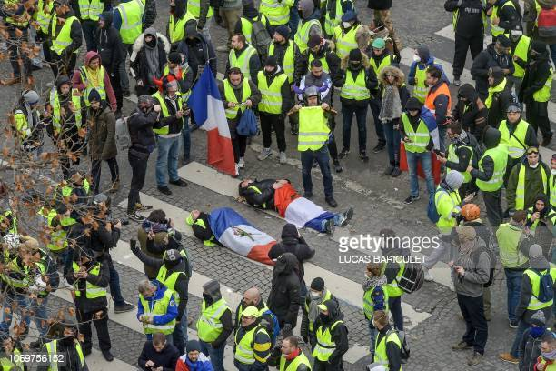 Protestors wrapped in French flags lie on the ground near riot police on the Champs Elysees avenue in Paris on December 8, 2018 during a protest of...