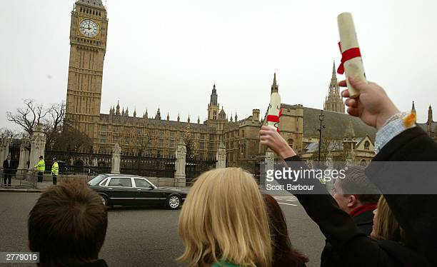 Protestors yell and hold fake degrees aloft as the motorcade of Britain's Prime Minister Tony Blair enters the Houses of Parliament December 3 2003...