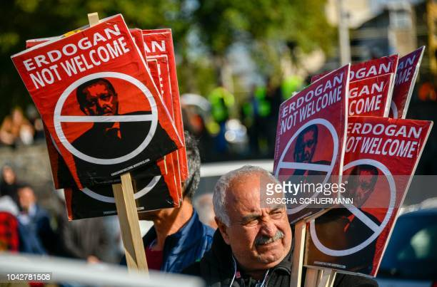 A protestorstands with placards reading Erdogan not welcome during a demonstration called Erdogan not welcome on the banks of the river Rhine in...