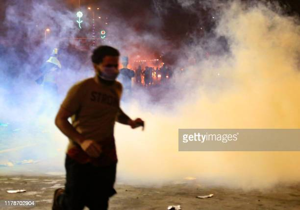 Protestr runs from tear gas smoke during anti-government protests in the Shiite shrine city of Karbala, south of Iraq's capital Baghdad, late on...