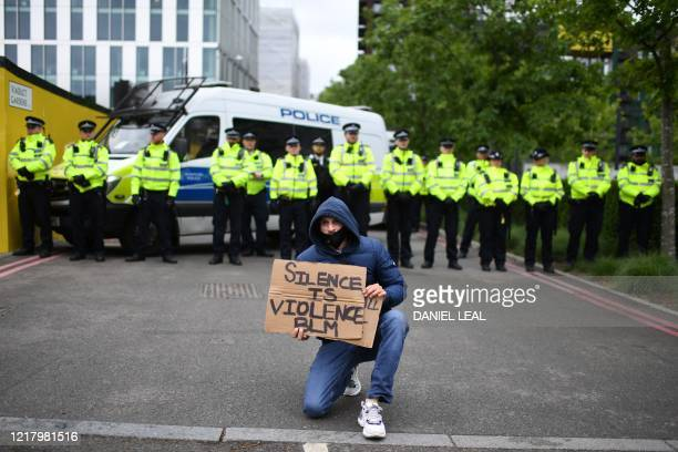Protetr shouts slogans in front of a line of police officers near the US Embassy in south west London on June 6 during a protest action to show...