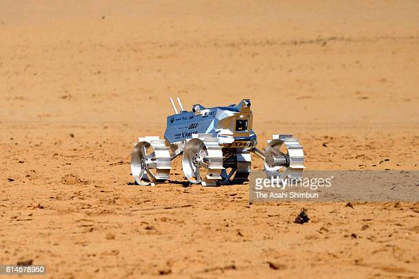 A prototype of an unmanned lunar rover developed by Hakuto navigates near a mock rock during a field test on the Tottori Sand Dunes on September 27...