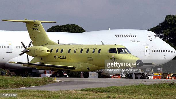 A prototype of India's first locallybuilt 14seater civilian aircraft passes by a Boeing 737200 transport aircraft 22 August 2004 on the tarmac of the...