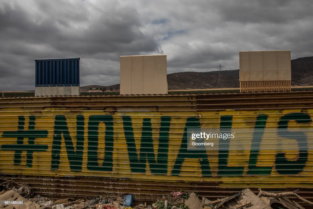 Prototypes for the new U.S. -Mexico border wall stands on display behind a fence with grafitti that reads 'No Walls' in Tijuana, Mexico, on Monday, May 21, 2018. 'We won't care about threats of a wall,' National Regeneration Movement Presidential candidate Andres Manuel Lopez Obrador announced, assuring another rally crowd in Zacatecas, one of the states that sends the most migrants to the U.S., that with him in power, they'll achieve equal footing with their neighbors to the north. Photographer: Alejandro Cegarra/Bloomberg via Getty Images