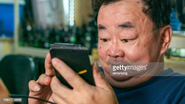 protrait of a short sighted man using mobile phone - close to stock pictures, royalty-free photos & images