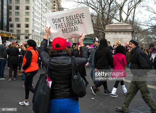 A proTrump counter demonstrator holds up a sign saying 'Don't Believe The Liberal Media' during the Women's March on January 20 2018 in New York City...