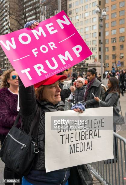A proTrump counter demonstrator holds up a sign saying 'Women For Trump' and 'Don't Believe The Liberal Media' during the Women's March on January 20...