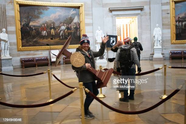 Pro-Trump protester carries the lectern of U.S. Speaker of the House Nancy Pelosi through the Roturnda of the U.S. Capitol Building after a pro-Trump...
