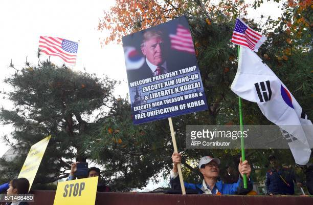 A proTrump supporter holds a placard showing a picture of US President Donald Trump as he waits for Trump outside the National Cemetery in Seoul on...