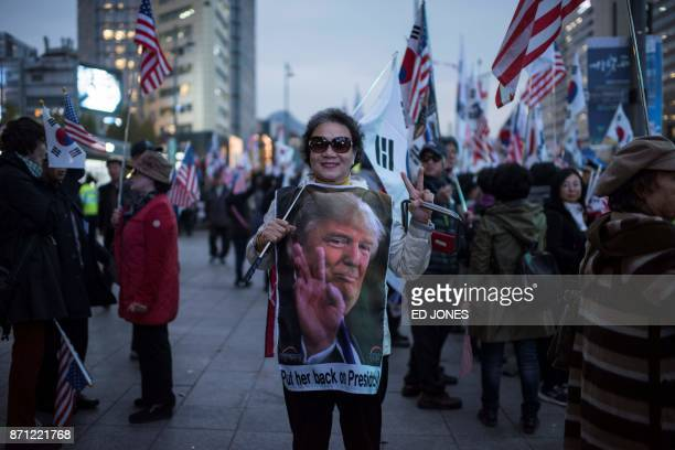 A proTrump supporter of impeached former South Korean president Park GeunHye holds a South Korean flag and wears a Donald Trump shirt as she waits...