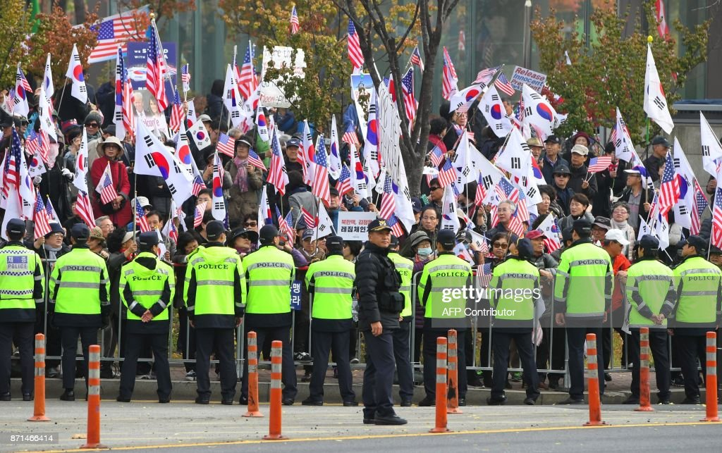 Pro-Trump supporters wave the US and South Korean flags as they wait for US President Donald Trump outside the National Cemetery in Seoul on November 8, 2017. Trump declared on November 8 that 'now is the time for strength' on nuclear-armed North Korea, calling for all countries to join forces against the regime. / AFP PHOTO / JUNG Yeon-Je