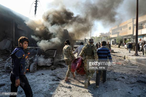 Pro-Turkish Syrian fighters carry away remains of the victims of a car bomb explosion at the industrial zone in the northern Syrian town of Tal...