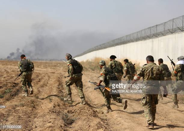 TOPSHOT ProTurkish Syrian fighters cross the border into Syria as they take part in an offensive against Kurdishcontrolled areas in northeastern...