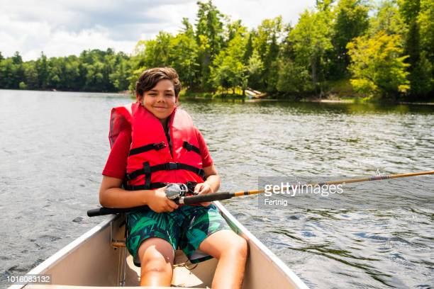 a proud 10 year-old boy holds up a big largemouth bass he caught. - 10 11 anni foto e immagini stock