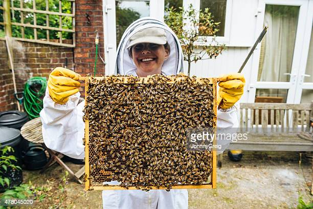 Proud apiarist with bees and honeycomb from hive